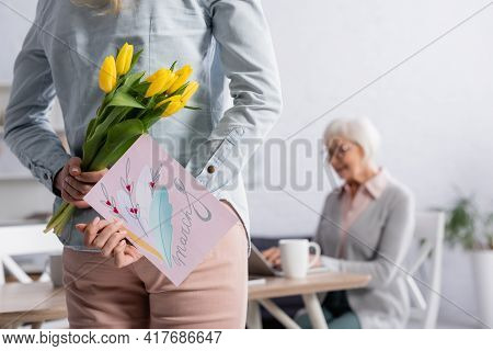 Woman Hiding Flowers And Greeting Card With 8 March Lettering Near Mother On Blurred Background.