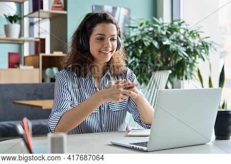 Young Adult Happy Smiling Hispanic Indian Student Wearing Headphones Talking On Online Chat Meeting