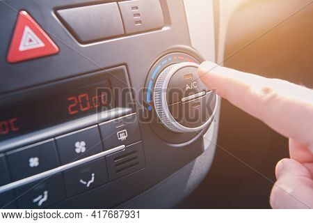 Man Hand Switches On The Air Conditioning In The Car. Driver Turning On Car Climate Control System.