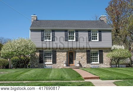 Two Story Home with Gray Siding and Tan Stone in Spring