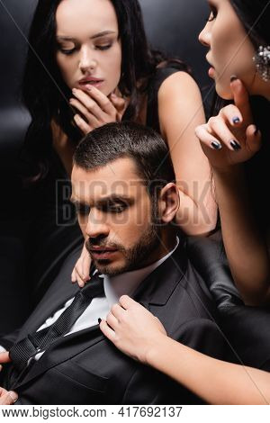 Passionate Women Seducing Young Businessman In Suit On Black.