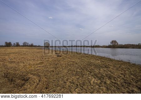 A Flooded Field On The Outskirts Of The Village, The Sky Is Reflected In The Water. Trees And Bushes