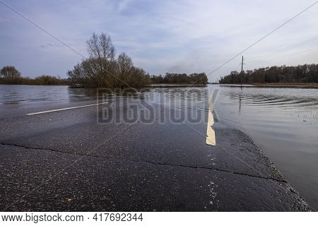 The Road Is Under Water Due To Flooding. The River Overflowed Its Banks And Flooded The Road. Asphal