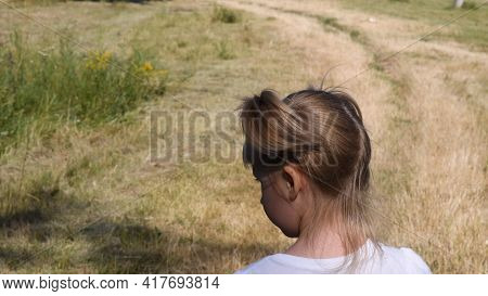 Toddler Girl Turns Her Head With Funny Ponytail. Kid Girl In White T-shirt At Background Of Country