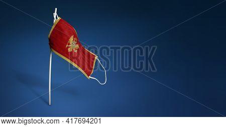 Montenegro Mask On Dark Blue Background. Waving Flag Of Montenegro Painted On Medical Mask On Pole.
