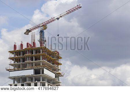Construction Site. A Large Construction Crane Against A Blue Sky Builds A House. A High-rise Buildin