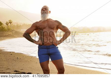 Happy Fit Senior Man Showing His Muscle On The Beach After Outdoor Workout, During Sunset Time.