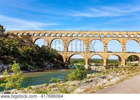 Picturesque antique bridge - aqueduct. The Pont du Gard is the tallest Roman aqueduct. Interesting trip to France. The shallow Gardon River.