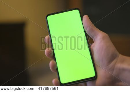 Isolated Human Hand Holding A Green Screen Smartphone, Hi Tech Addiction Concept