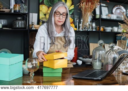 Beautiful Aged Woman In Eyeglasses And Apron Sitting At Counter And Packing Decor And Glassware Into