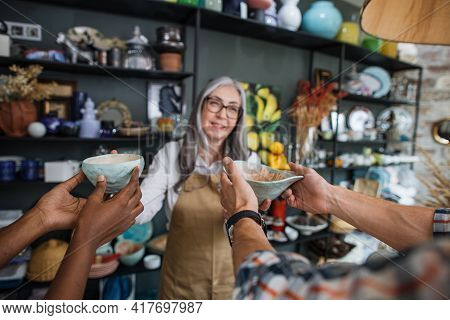 Close Up Of Multiracial Man And Woman Choosing Decor At Modern Store. Competent Aged Saleswoman Show