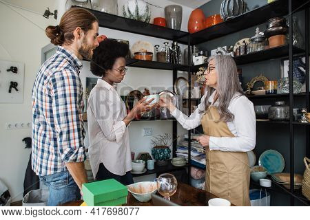 Beautiful Multiracial Couple Visiting Modern Store For Choosing Decor Products For Their House. Aged