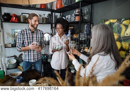 Happy Caucasian Man And African Woman Listening To Gray-haired Saleswoman While Choosing Exclusive C