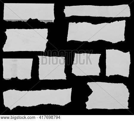 Ten pieces of torn newspaper on black background