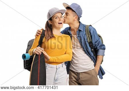 Male student kissing a female skater with a longboard isolated on white background