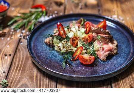 Beef Tenderloin Fried On Fire With Herbs, Seasoned With Spices, Tomatoes. Wooden Brown Background De