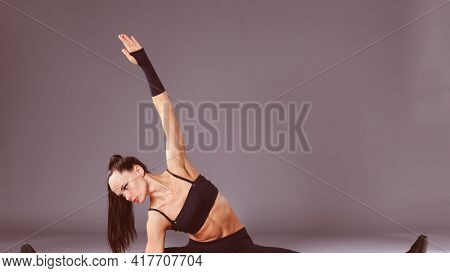 Muscular young woman standing on gray background. Muscular young woman. beautiful girl doing sport exercises
