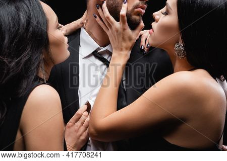 Hot, Elegant Women Seducing Young Man In Suit Isolated On Black.