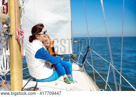 Mother And Baby Boy Sail On Yacht In Sea. Family Sailing On Boat. Mom And Kid In Safe Life Jacket Tr