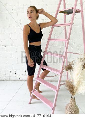 Beautiful Young Woman Wearing Black Sports Bra And Knee Length Leggings