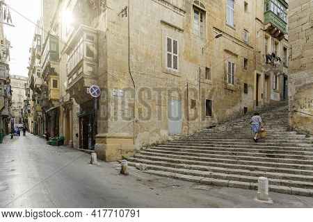 Valletta, Malta - February 20, 2010. Local People Walk Pass Small Shops And Cafes. Old Fashioned Bal