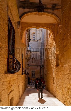Mdina, Malta - February 18, 2010. Tourists Walk On Ancient Narrow Streets In Mdina. Old Buildings Wi