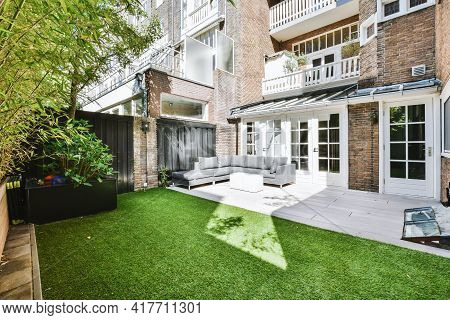 Yard With Sofa And Green Lawn Located Outside Brick House On Sunny Summer Day