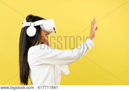 Black Asian Woman Wearing Vr Headset Over Yellow Background To Get Excite Experience Of Virtual Real