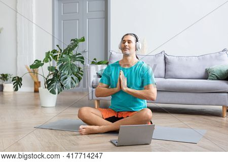 Meditating At Home - Using From The Internet To Monitor The Workout. He Listens To Relaxing Meditati