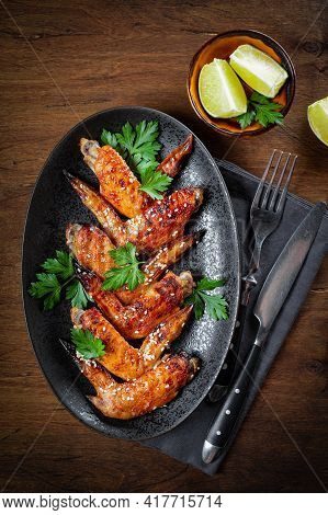 Baked Chicken Wings With Sesame Seeds, Parsley And Lime On A Black Plate Top View, Vertical Photo