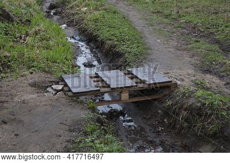 A Small Homemade Wooden Bridge Over A Muddy, Smelly Puddle Or Stream In A Slum. Unkempt Area, Outski