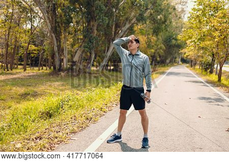 A Tired Young Man Wipe The Sweat. Man Resting, Breathing And Holding A Bottle Of Drinking Water On T