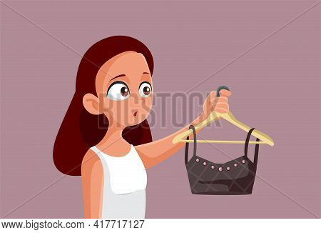 Teen Girl Holding A Crop Top On A Clothing Hanger