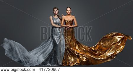 Fashionable Two Woman In Golden Evening Dress And Silver Gown. Glamour Beauty Model Fashion Prom Clo