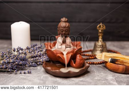 Religious Concept. Buddha Figurine With Incense Smoke. Buddha Statue With Candle Burning And Incense