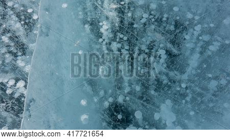 Ice, Close-up, Details. Cracks Are Visible On The Transparent Shiny Surface. Columns Of Frozen Metha