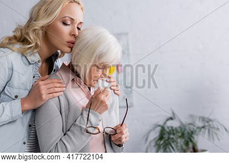 Woman Calming Disappointed Mother With Eyeglasses And Napkin.