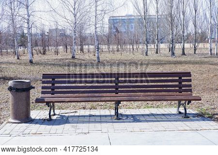 An Empty Brown Wooden Bench With An Urn. Park Bench In Early Spring. A Bench Against The Background