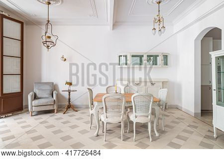 Dining Table In A Center Of Living Room Decorated In Retro Style. Tile Floor And Vintage Chandeliers
