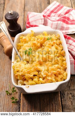 pasta and cheese gratin on wood background
