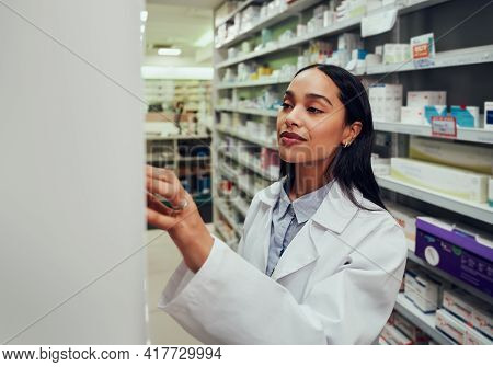 Young Woman Pharmacist Wearing Labcoat Searching For Medicine In Shelf In Chemist