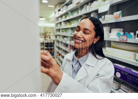 Cheerful Female Pharmacist Wearing Labcoat Searching For Medicine In Shelf In Chemist