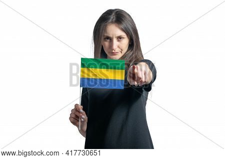 Happy Young White Woman Holding Flag Of Gabon And Points Forward In Front Of Him Isolated On A White