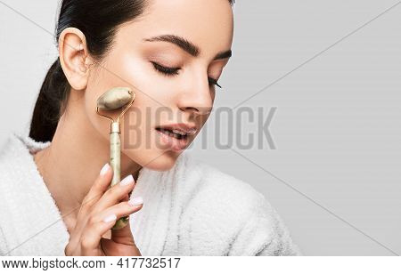 Facial Jade Roller. Young Woman Massages Her Face Using A Green Jade Roller For Elastic Perfect Skin