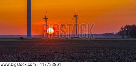 Wind Turbines For Renewable Energy In An Agricultural Field In Bright Orange Yellow Sunlight At Sunr