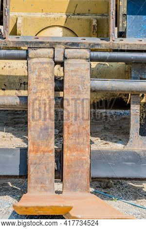 Front View Of Rusty Steel Forks On Industrial Forklift At Construction Site.