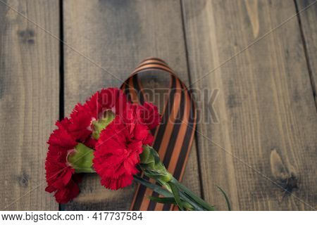 Three Red Carnations With A St. George Ribbon On A Wooden Background. Georgievsk Ribbon - Russian Sy