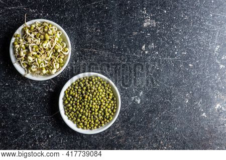 Sprouted green mung beans and dried beans. Mung sprouts in bowl on black table. Top view.