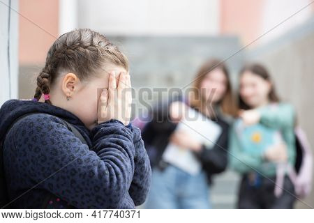 Girl being bullied at the school. Educational school isolation and bullying concept.
