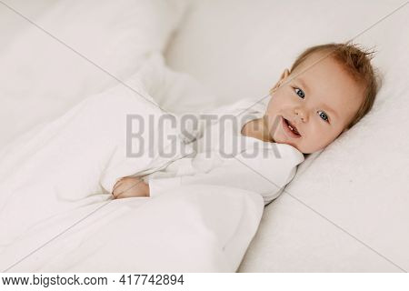 The Kid Lies In A Snow-white Bed Under The Covers, Laughs And Indulges